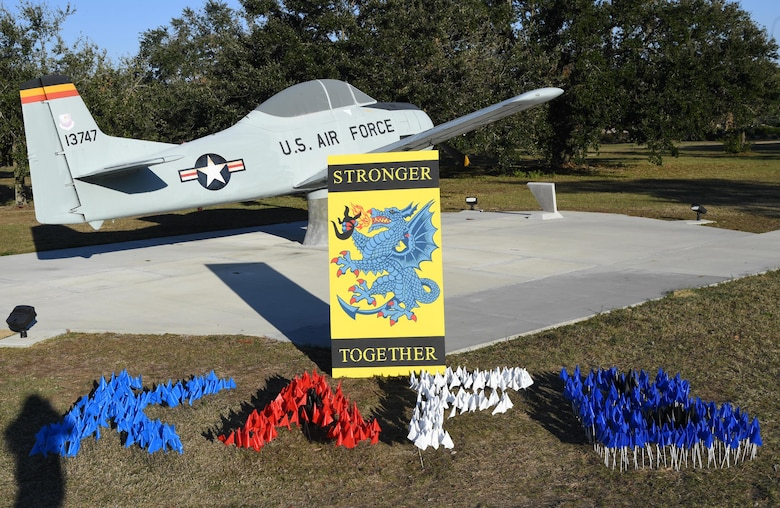 "Flags are displayed inside the letters, KAFB, at Heritage Field during the Dragon March at Keesler Air Force Base, Mississippi, Dec. 8, 2020. The theme of the three-mile walk was ""Stronger Together."" (U.S. Air Force photo by Kemberly Groue)"