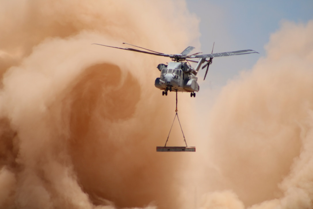 An aircraft flies through a cloud of dust while carrying an object.