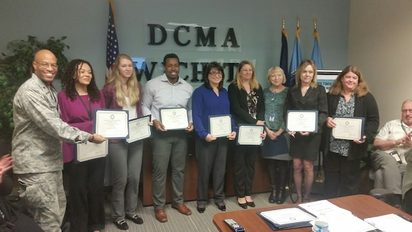 Ten people hold certificates standing in front of a D C M A Wichita sign.