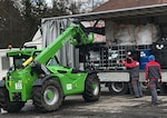 Men load bags onto a truck.