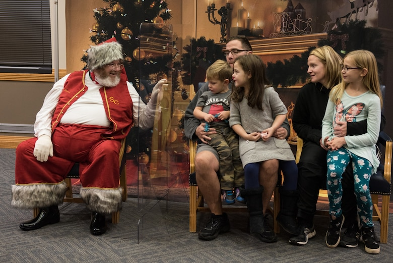 The Lawter family met with Santa Claus at the annual Christmas Tree Lighting Ceremony at Whiteman Air Force Base, Missouri, Dec. 8, 2020. Attendees met with Santa by sitting apart from him and safely distancing from others to prevent the spread of COVID-19. (U.S. Air Force photo by Airman 1st Class Christina Carter)
