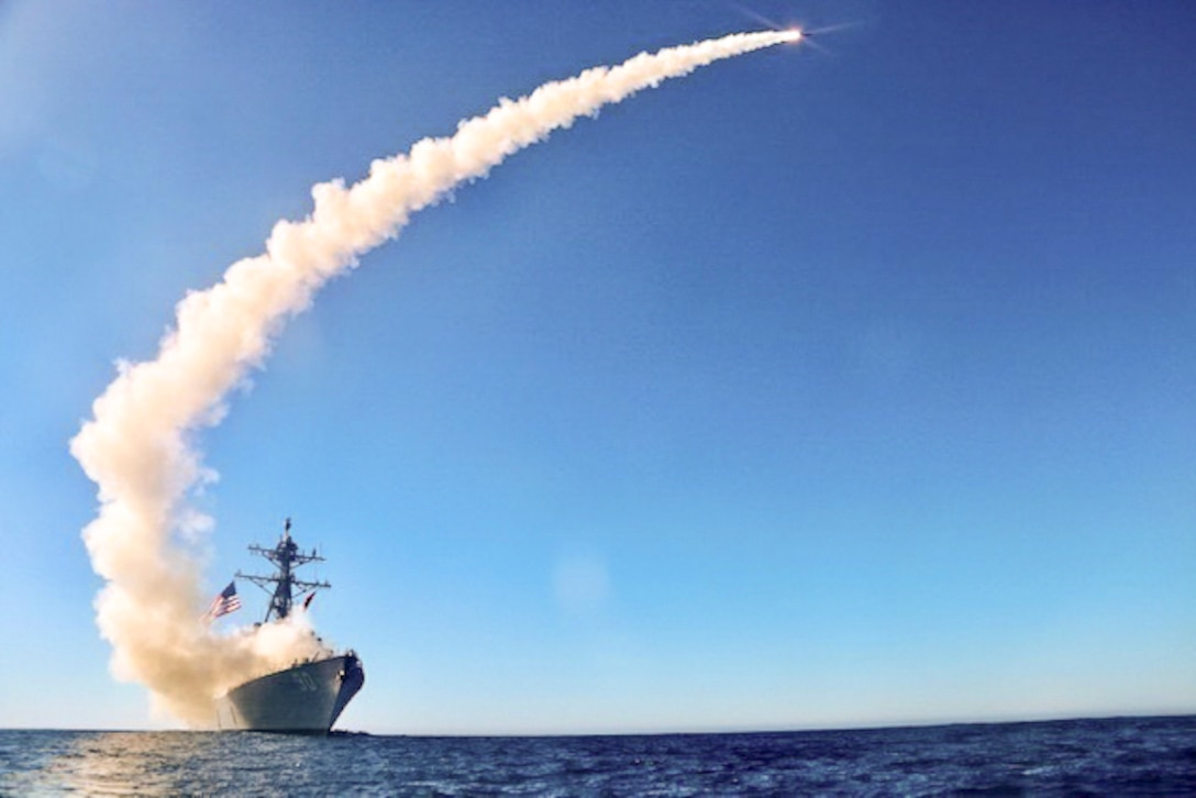 A missile shoots from a ship, created a curved cloud trail in blue sky.