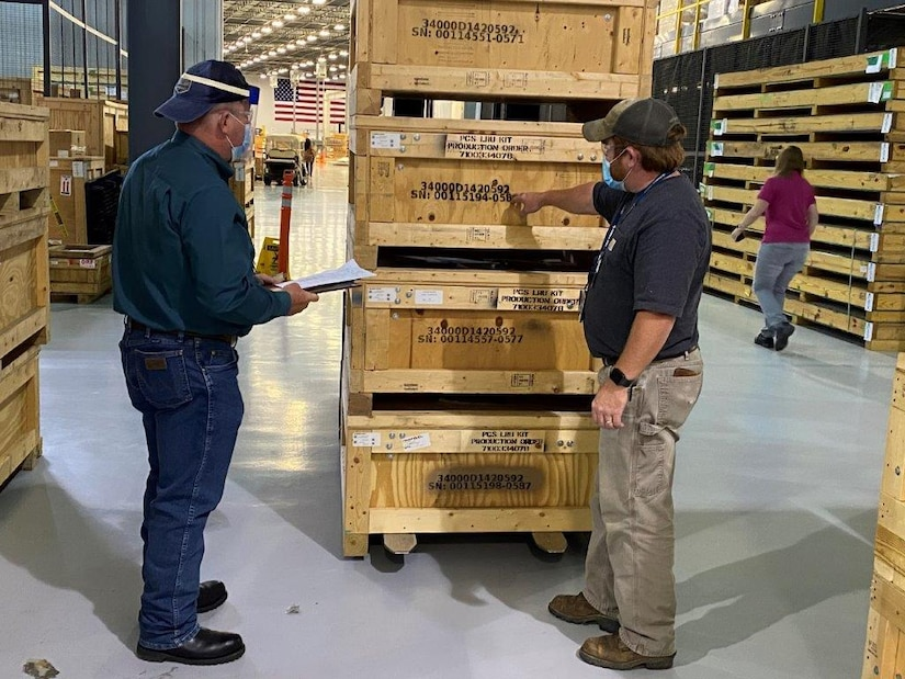 Two men stand in front of pallets and discuss paperwork