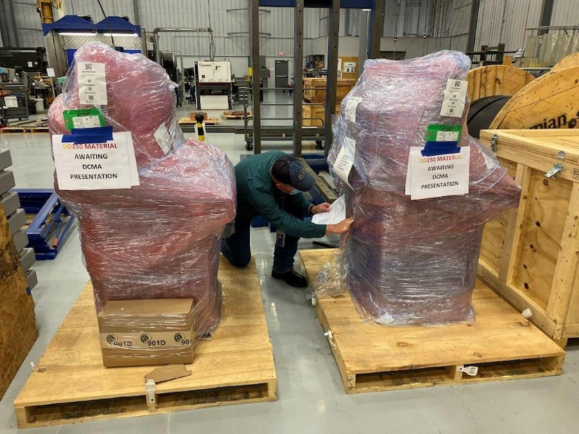 A man kneels down between two large wooding shipping pallets to check paperwork