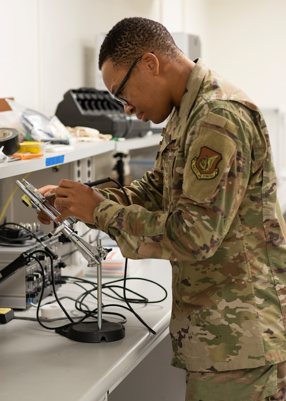 Airman 1st Class Samuel Wambuzi, 36th Maintenance Squadron aircraft, electrical and environmental journeyman, uses a soldering iron to melt pieces and reattach new solder to fix the circuit board at Andersen Air Force Base, Guam, Dec. 3, 2020. Wambuzi is one of the five Airmen that work on the Air Force Repair Enhancement Program here, fixing technology and equipment across the base, saving and making the 36th Wing thousands yearly. (U.S. Air Force photo by Senior Airman Aubree Owens)