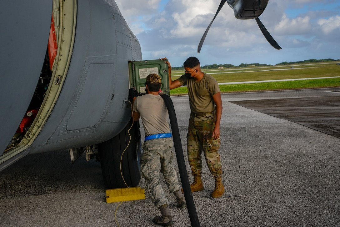 Senior Airman Stephen Yarbrough (left), 374th Aircraft Maintenance Squadron crew chief out of Yokota Air Base, Japan, and Airman 1st Class Andre Anderson, 36th Logistics Readiness Squadron fuel distribution operator, attaches a fuel hose to C-130J Super Hercules during Operation Christmas Drop 2020 at Andersen Air Force Base, Guam, Dec. 9.
