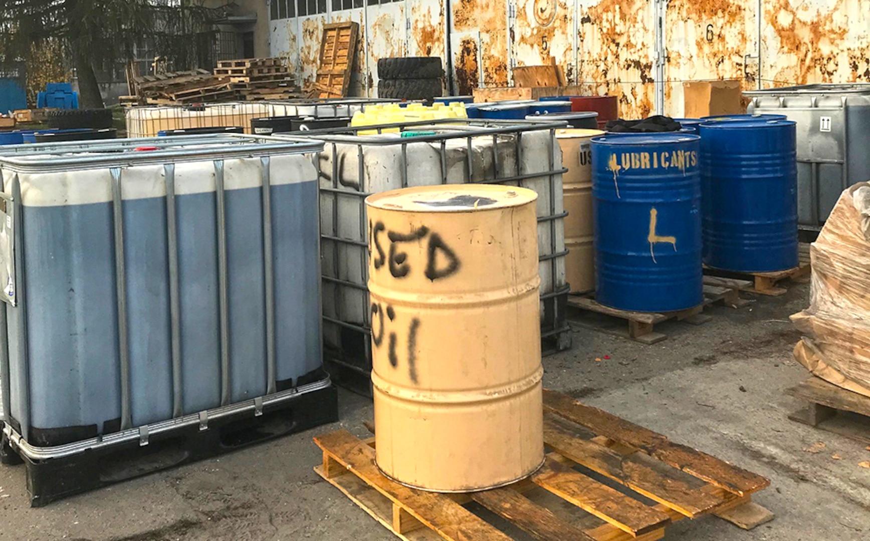 Barrels of fluids sit in a parking lot.