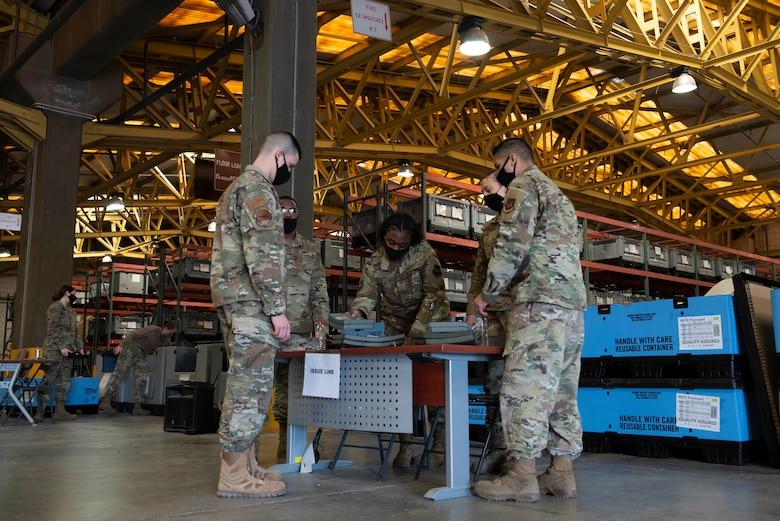 Four Airmen exchange armor plates in an equipment warehouse.