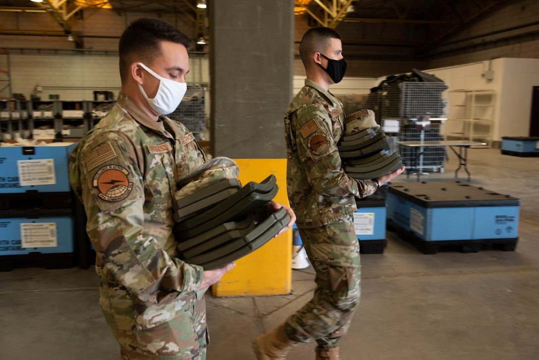Two Airmen walking through a warehouse carrying heavy armor plates.