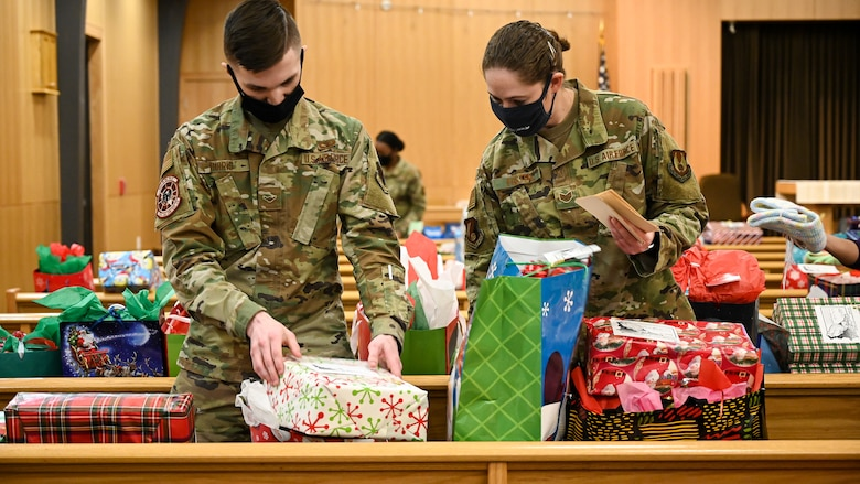 Volunteers sort Angel Tree wrapped gifts on pews inside the base chapel.