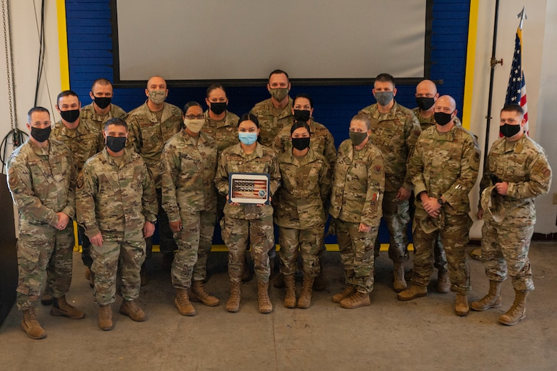 Photo of Airmen standing with an award