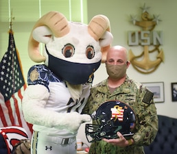 Master Chief Petty Officer of the Navy (MCPON) Russell Smith poses for a photo with Bill the Goat, the United States Naval Academy mascot.