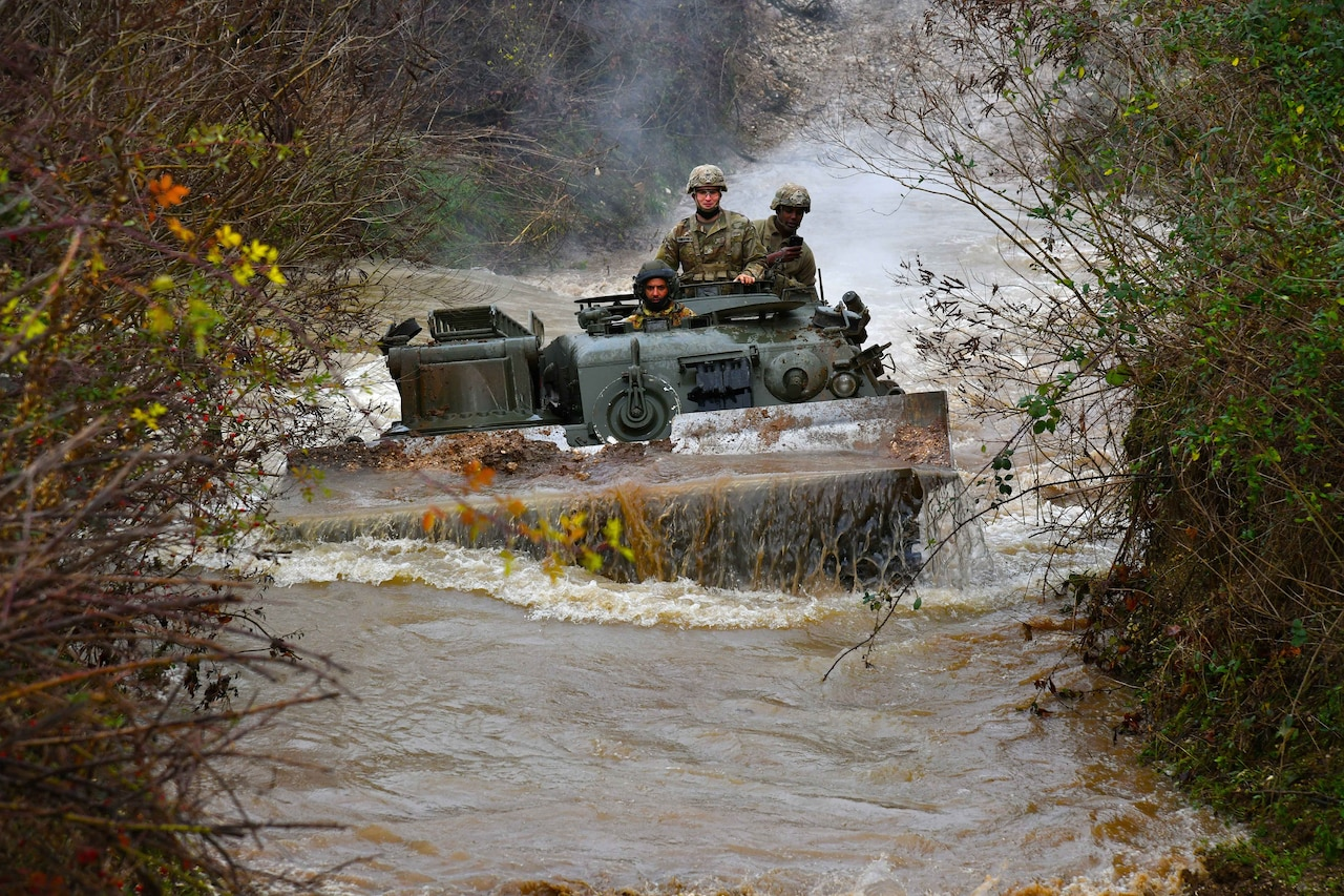 U.S. and Italian troops operate a vehicle through water in the woods.