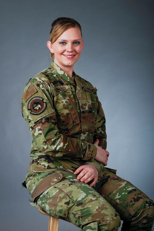 A female Airman sits on a stool looking at the camera smiling.