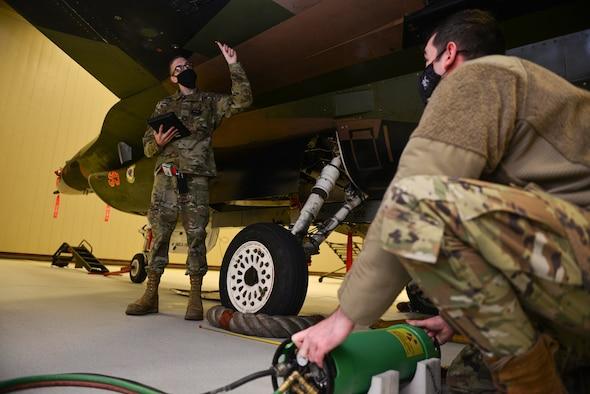 U.S. Air Force Senior Airman Timothy Carlson, a 354th Maintenance Squadron non-destructive inspection (NDI) journeyman, guides Staff Sgt. Zachary Chambers, a 354th MXS NDI craftsman, as he aligns an x-ray tubehead on Eielson Air Force Base, Alaska, Dec. 9, 2020