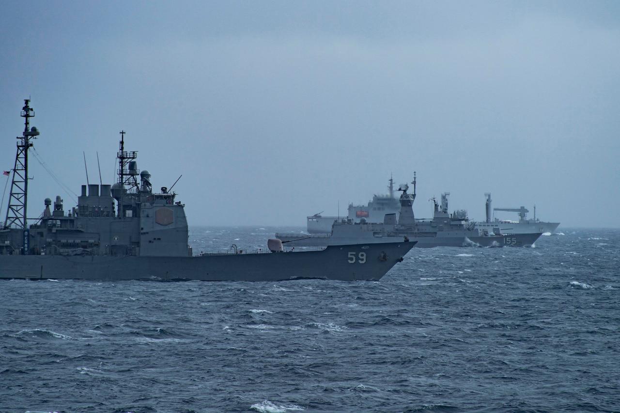 Ships sail alongside each other on the ocean.