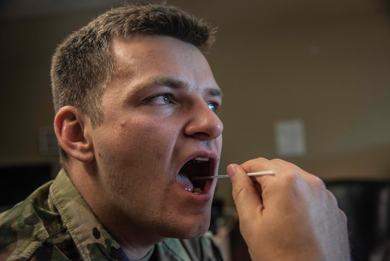 An Airman swipes a cotton swab on the inside of his cheek to collect DNA.