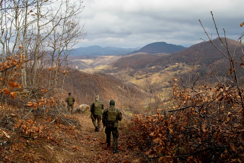 Soldiers walk down a mountain trail.