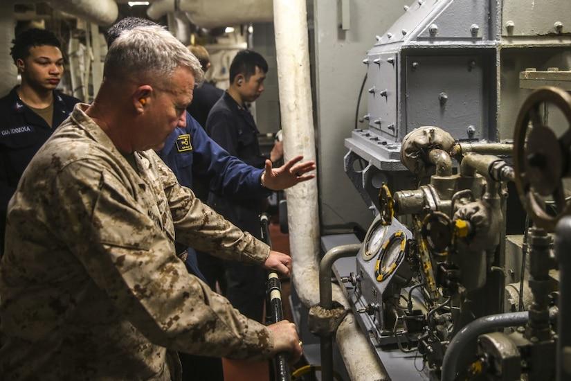 A man in a Marine Corps uniform tours a ship.