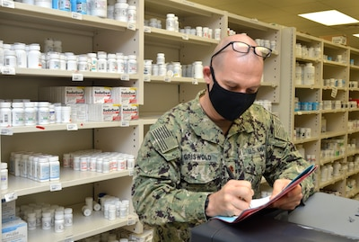Lt. Cmdr. Jeremy Griswold, assistant department head for Naval Hospital Jacksonville�s pharmacy, reviews prescriptions at the outpatient pharmacy.