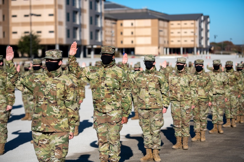 Graduates of basic training raise their right hands as they take the oath of enlistment.