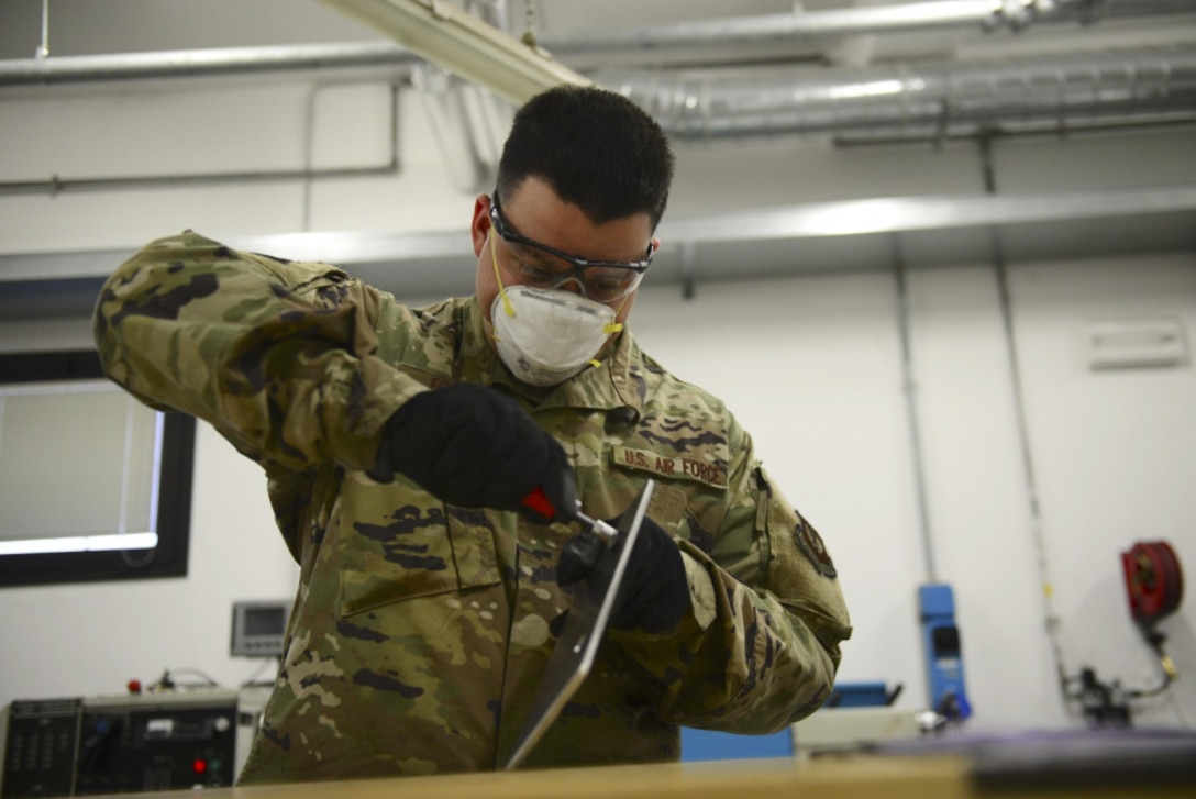 Airman 1st Class Joshuah Fonteno, 31st Maintenance Squadron Aircraft Metals Technology Journeyman, works on a piece of metal at Aviano Air Base, Italy, Dec. 3, 2020. Fonteno has used the extra time he's gained from COVID-19 conditions to improve himself by setting personal and professional goals. (U.S. Air Force photo by Tech. Sgt. Tory Cusimano)