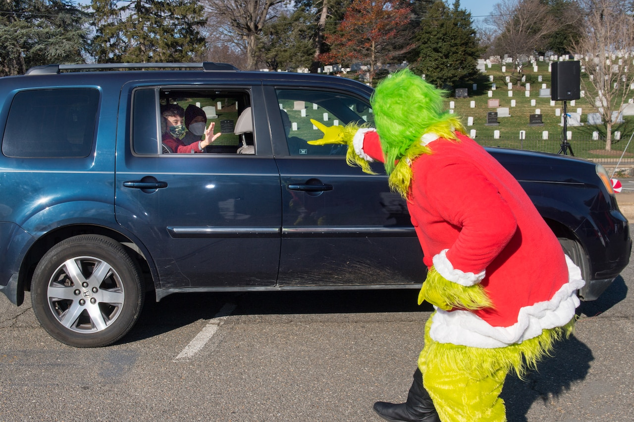 A man dressed as the Grinch waves to two boys in the back seat of an SUV.