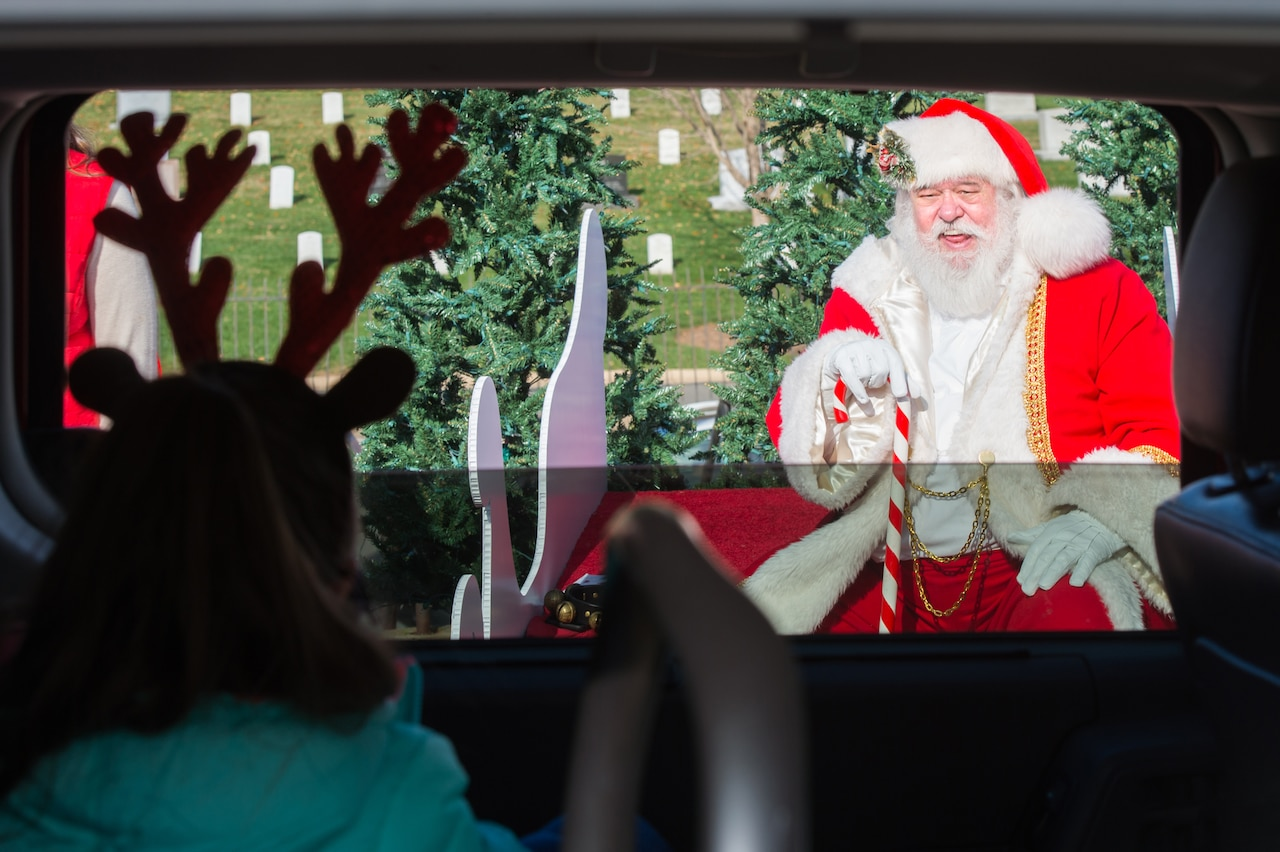 A child in reindeer ears looks out an open car window at Santa.