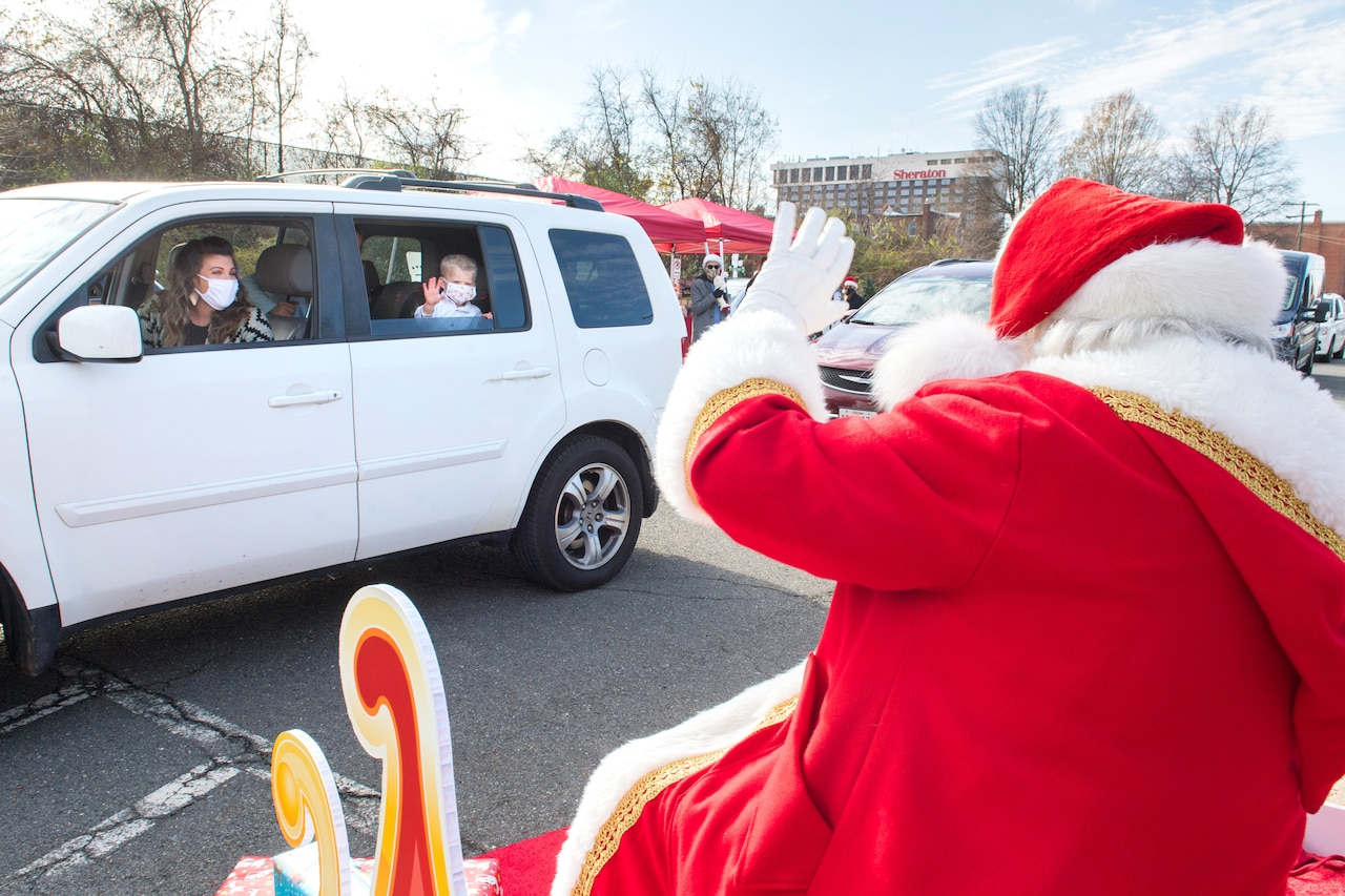 Santa waves to a masked family in an SUV.