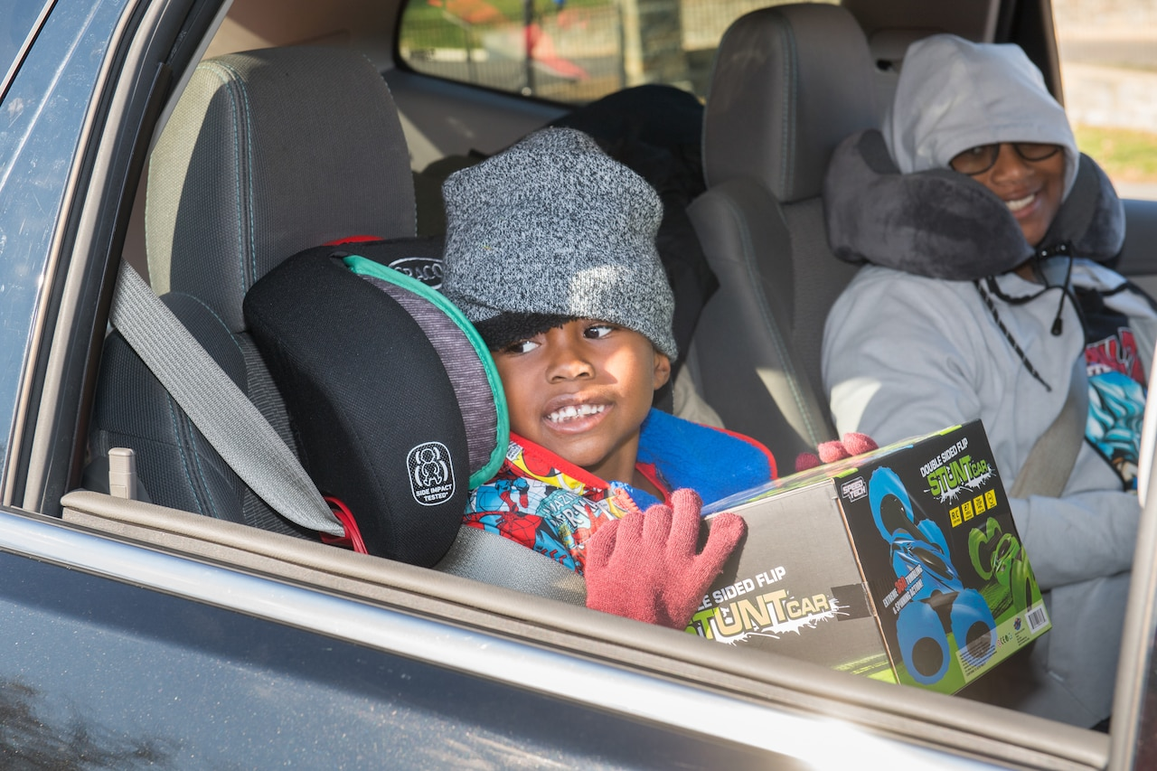 A small child sits in a car holding a box while a woman smiles beside him.