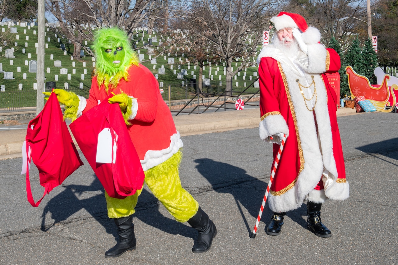 A man dressed as the Grinch slinks away from Santa as he holds two large red bags.