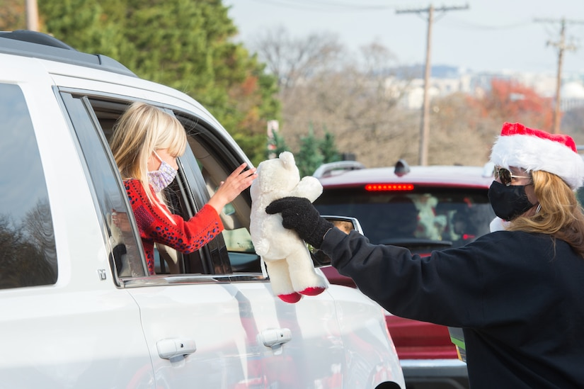 A woman hands a stuffed animal to a child through a car window.
