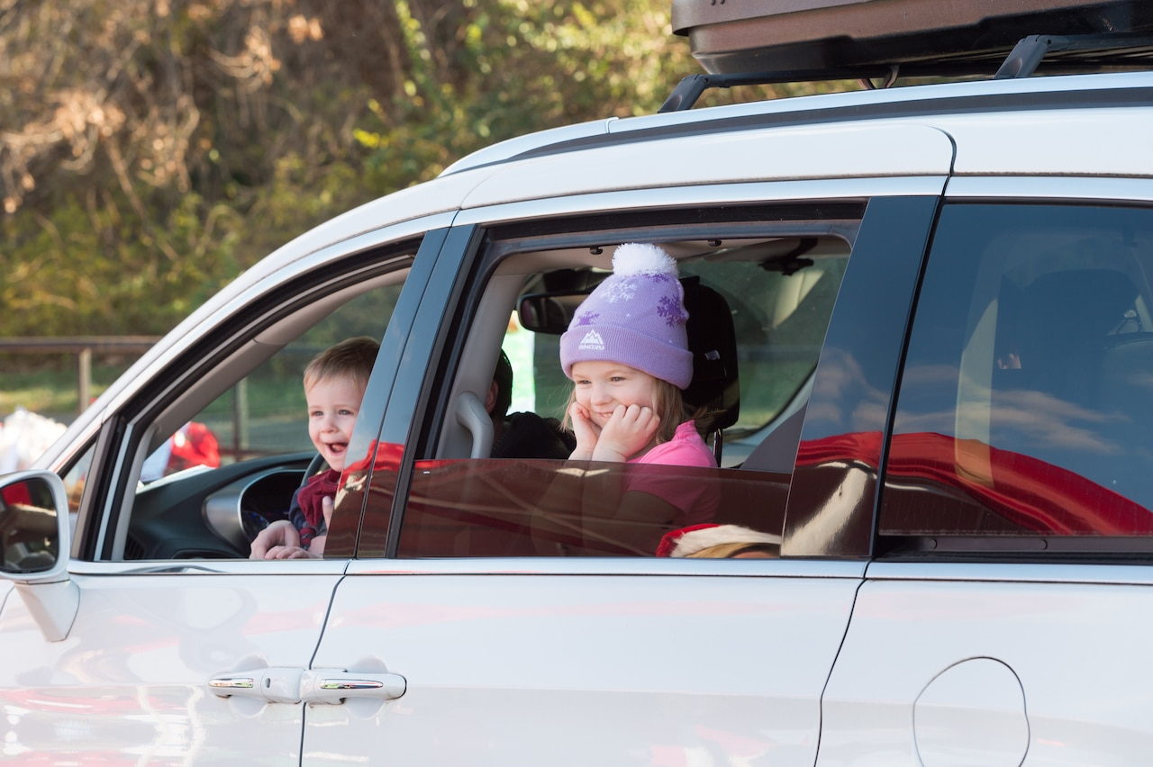 Two small children smile while looking out of their SUV.