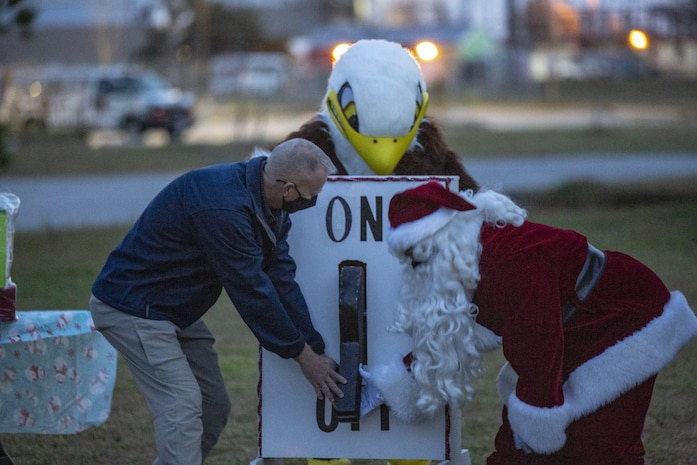 U.S. Marine Corps Col. Curtis V. Ebitz, left, the commanding officer of Marine Corps Air Station New River, and Santa flip the switch for the 8th annual tree lighting ceremony on Marine Corps Air Station New River, North Carolina, Dec. 6, 2020. The annual celebration brings service members and their families together to start the holiday season. (U.S. Marine Corps Photo by Lance Cpl. Isaiah Gomez)