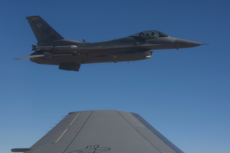 An F-16 Fighting Falcon from the 49th Wing at Holloman Air Force Base (AFB), New Mexico, flies off the left wing of a KC-46 Pegasus from the 56th Air Refueling Squadron at Altus AFB, Oklahoma, December 7, 2020. A two-ship KC-46 refueler formation flew in a racetrack pattern over southern New Mexico while refueling ten F-16s from Holloman AFB. (U.S. Air Force photo by Tech. Sgt. Robert Sizelove)