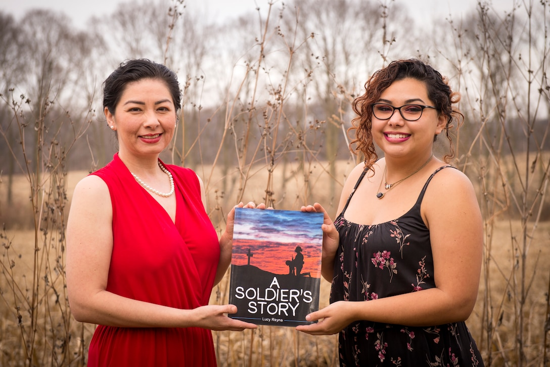 Tech. Sgt. Lucille Reyna, 434th Air Refueling Wing paralegal, and her daughter Sienna Urbina, right, pose for a photo with their children's book 'A Soldier's story' at their residence in Logansport, Indiana, Dec. 11, 2020. The 28-page book highlights what a service member may experience while on a deployment in a child-friendly way. (U.S. Air Force photo/Master Sgt. Ben Mota)