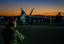 U.S. Navy Airmen stand on the flight line during take-off at night.