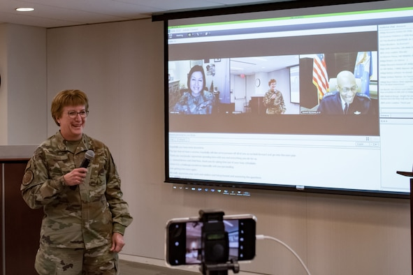 Image of an Airman talking in front of a screen.