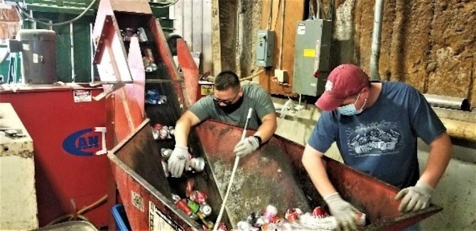 Jesse Vasquez and Mickey Lyles, City of Altus employees at the 97th Air Mobility Wing Recycling Center on Altus Air Force Base, Oklahoma, sort cans to be crushed at the Altus Air Force Base recycling center Dec. 11, 2020. (U.S. Air Force photo by Judy Mott)