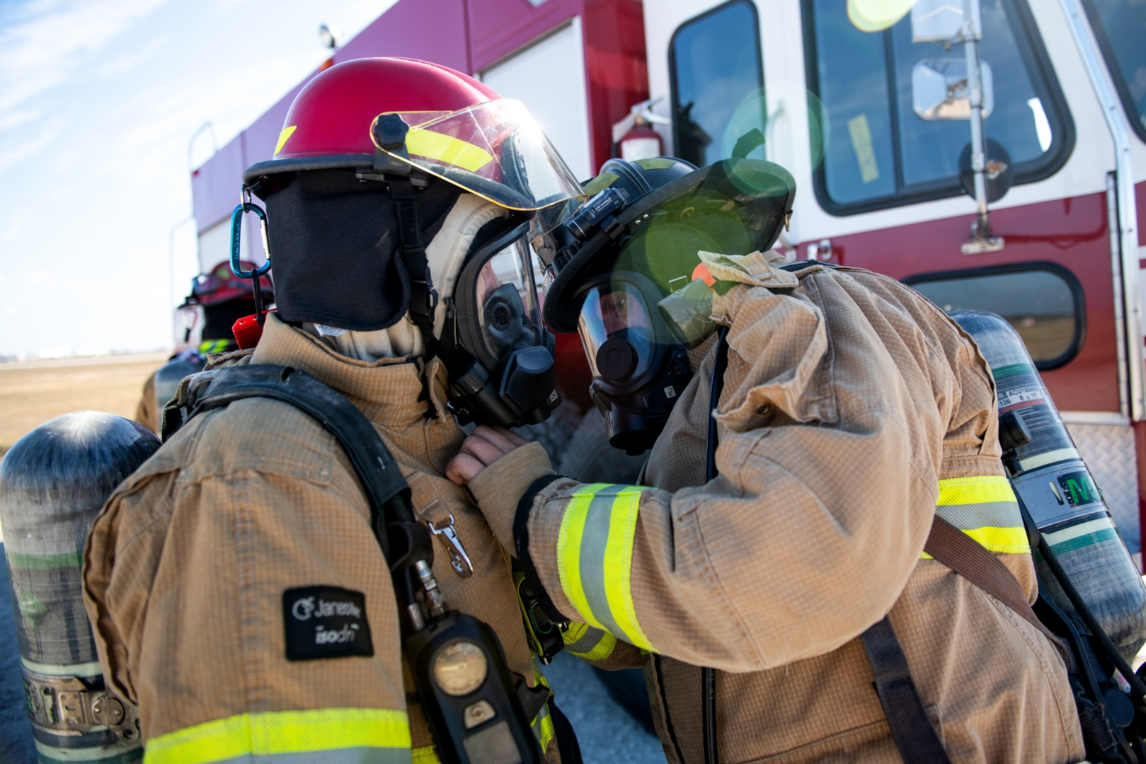 Two firefighters with Joint Base San Antonio conduct equipment checks prior to a live fire Aircraft Rescue Fire Fighting training Nov. 20, 2020, at Joint Base San Antonio-Lackland Kelly Field Annex.