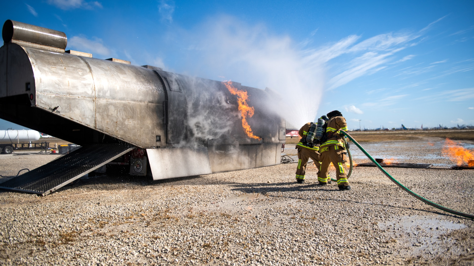 Andrew Sanchez assists Eric Flores, both firefighters with Joint Base San Antonio, during a live fire Aircraft Rescue Fire Fighting training Nov. 20, 2020, at Joint Base San Antonio-Kelly Field, Texas.