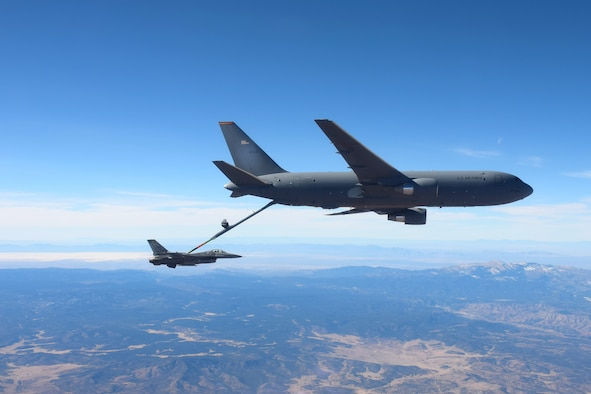 White Sands National Park can be seen in the distance at a KC-46 Pegasus from the 56th Air Refueling Squadron at Altus Air Force Base (AFB), Oklahoma, refuels an F-16 Fighting Falcon from the 49th Wing at Holloman AFB, New Mexico, December 7, 2020. Two KC-46s practiced air refueling operations over New Mexico with ten F-16s from Holloman AFB. (Courtesy photo by 1st Lt. Daniel Lee)