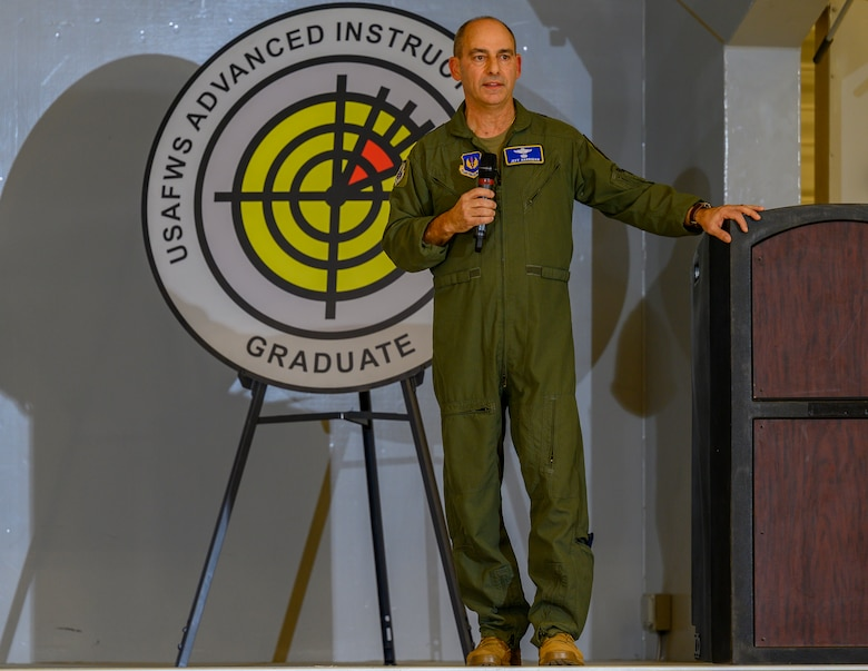 Airman stands on stage with microphone in hand