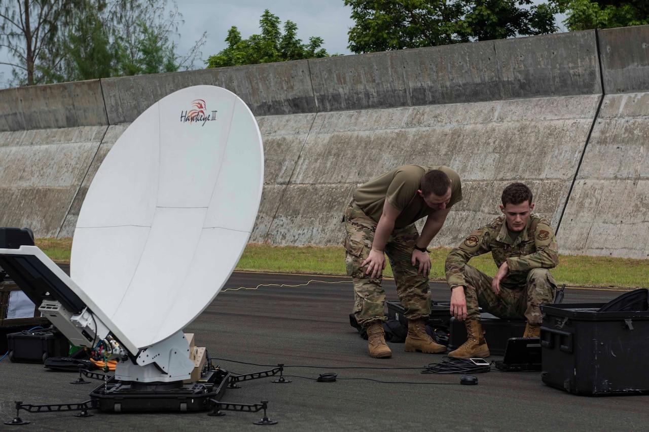 Airmen set up satellite gear.