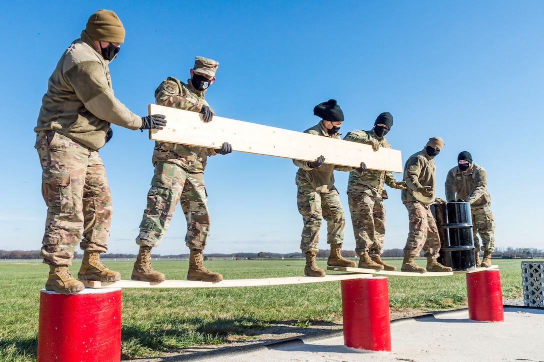 Airmen stand on an elevated plank while passing another plank to one another.