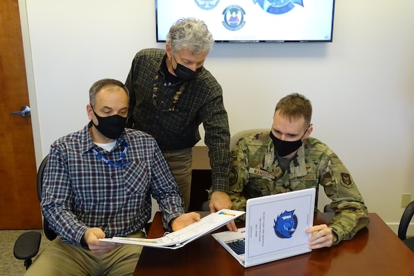 Jeff Efron (left) and Craig Diamantopoulos (middle), both space operations contractors from the Combined Force Space Component Command (CFSCC) operations directorate, look over past NASA recovery mission briefing books with Maj. Kyle Wamser, CFSCC chief of human space flight support on Dec. 7, 2020, at Vandenberg AFB, Calif. Wamser and his team most recently prepared these books for the CFSCC commander prior to the launch of the SpaceX Dragon Crew-1 'Resilience' Capsule on Nov. 16, 2020, where a crew of three Americans and one Japanese astronaut launched to the International Space Station. The briefing outlines the plan for astronaut rescue operations if an emergency arises and the astronauts make an unexpected landing anywhere in the world. The CFSCC commander oversees joint and multinational military support from Vandenberg AFB and is the final authority for rescue mission execution. (U.S. Air Force photo by Lt. Col. Mae-Li Allison)