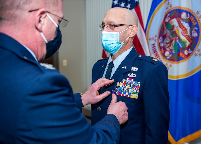 U.S. Air Force Maj. Allen Thill receives the Purple Heart award after sustaining injuries during his most recent deployment to Iraq in St. Paul, Minn., Dec. 12, 2020.