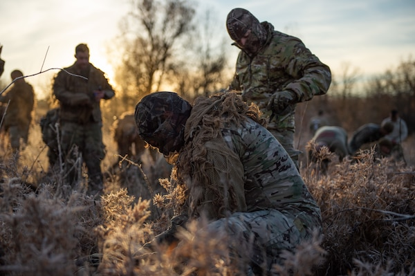 Staff Sgt. Demetrios Iannios, All Guard Sniper Team, California National Guard, leans down to double-check his equipment as his partner, Staff Sgt. Erik Vargas, adjusts his ghillie suit before they transform into the stealthiest hunters you never saw coming during the Stalk event on Dec. 9, 2020, at the 50th Winston P. Wilson and 30th Armed Forces Skill at Arms Meeting Sniper Championships at the Fort Chaffee Joint Maneuver Training Center. The championships were hosted by the National Guard Marksmanship Training Center with the help of the U.S. National Guard Sniper School Dec. 4-10, 2020.