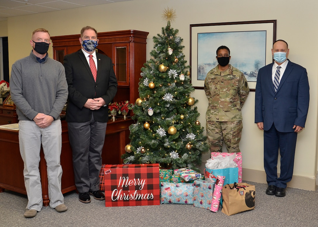 A group of four people, one of them in an Army uniform stand next to a Christmas tree in an office.