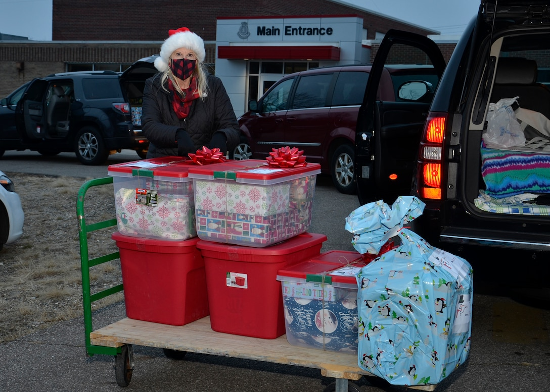 A woman stands next to a hand cart loaded with donated food and gifts for a family.